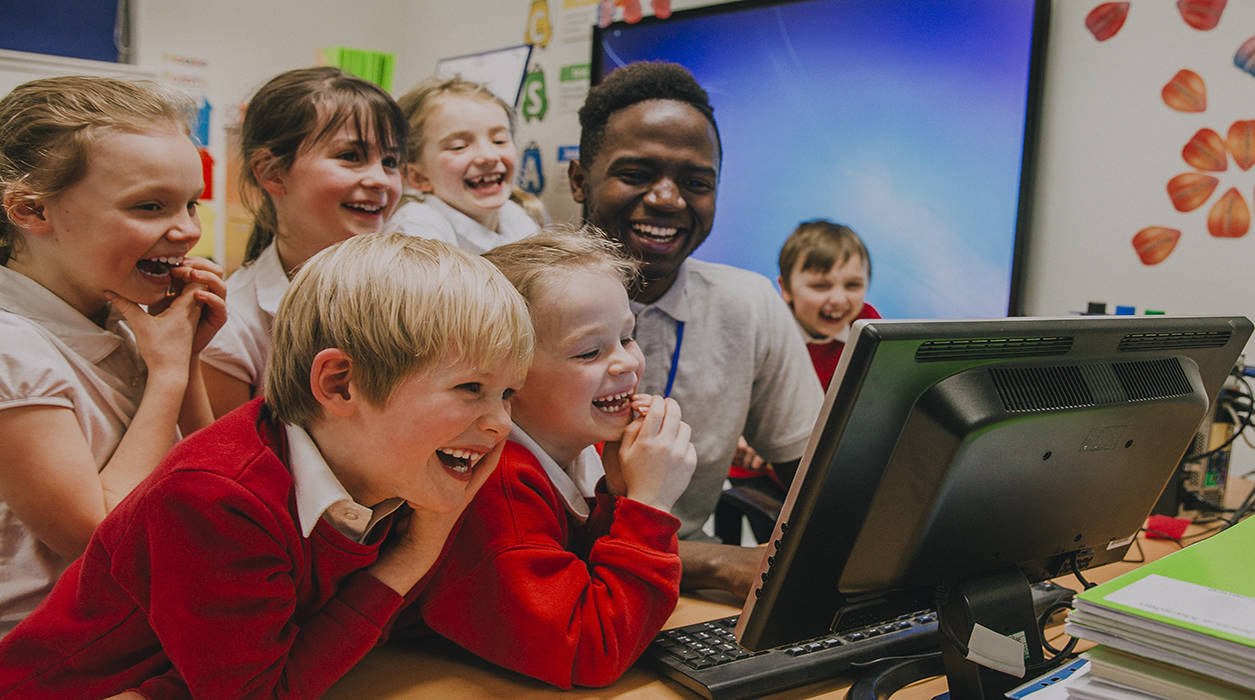 primary school children and their teacher laughing at the computer screen