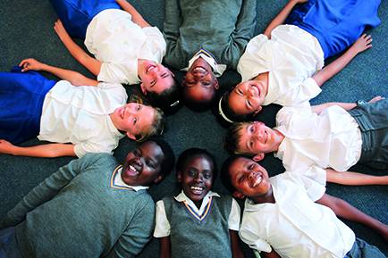 Primary pupils sitting in a circle smiling at the camera